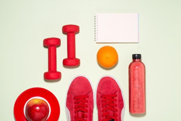 Концепция фитнеса. кроссовки, яблоко, гантели и бутылка фруктового сока на фоне пастельных тонов.