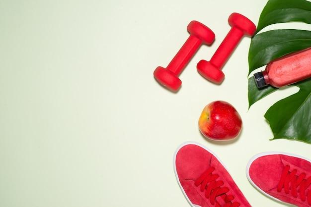 フィットネスのコンセプト。パステルカラーの背景にスニーカー、リンゴ、ダンベル、フルーツジュースのボトル。