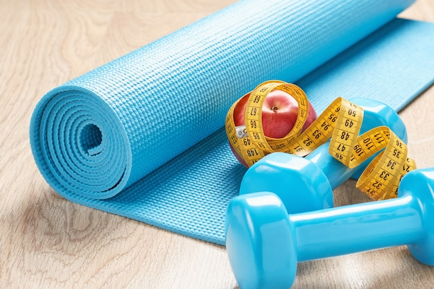 Fitness concept with blue dumbbells, fitness mat and a measuring tape