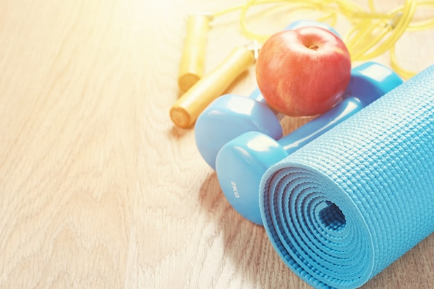 Fitness concept with a blue dumbbells and yoga mat, copy space