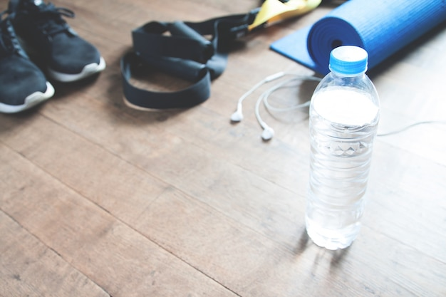 Fitness concept with bottle of water, sneakers, trx, yoga mat and earphones on wood floor, copy space