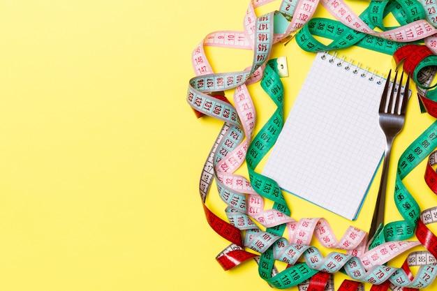 黄色の背景にあなたのデザインの空スペースでフィットネスの概念。カラフルなメジャーテープに囲まれたメモ帳とフォークの平面図