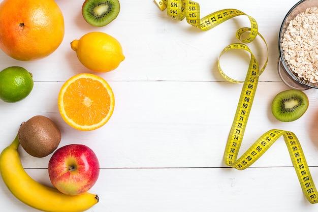 과일, 오트밀 한 그릇, 센티미터가 포함된 피트니스 개념. 상위 뷰 배경 개념입니다. 복사 공간