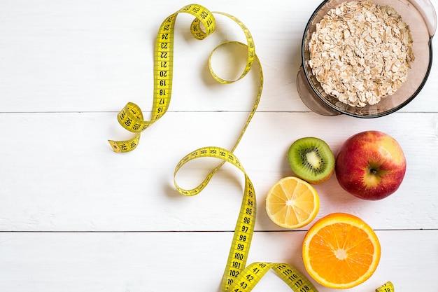 오트밀과 센티미터 상위 뷰 배경 개념의 과일 그릇과 피트니스 개념