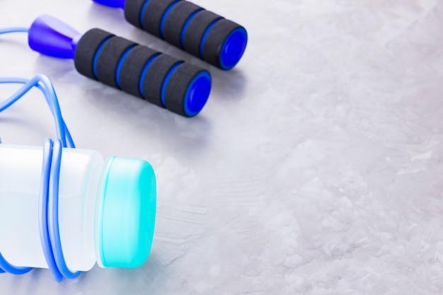 Концепция фитнеса со скакалкой и бутылкой воды
