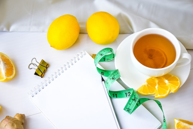 Fitness concept with lemon, ginger, chamomile tea, measuring tape on white background. empty notebook with copy space and pencil. healthy living concept. recipe.