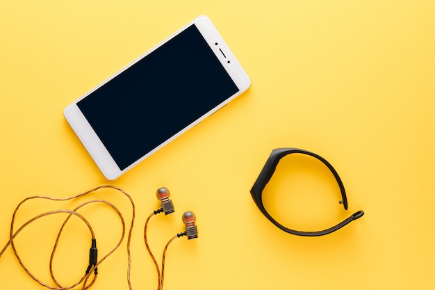 Fitness concept with mobile phone, earphones and fitness tracker on yellow background