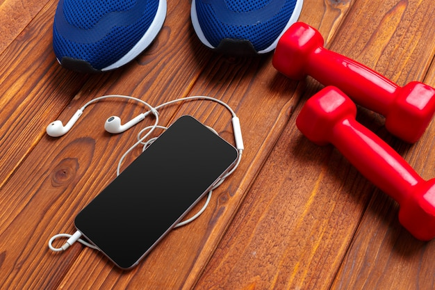 Fitness concept with sneakers, dumbbells