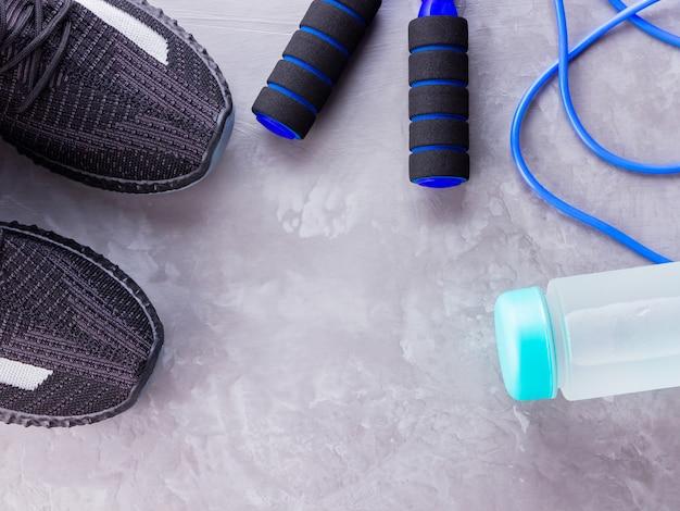 スニーカー、縄跳び、水のボトルとフィットネスの概念。上面図