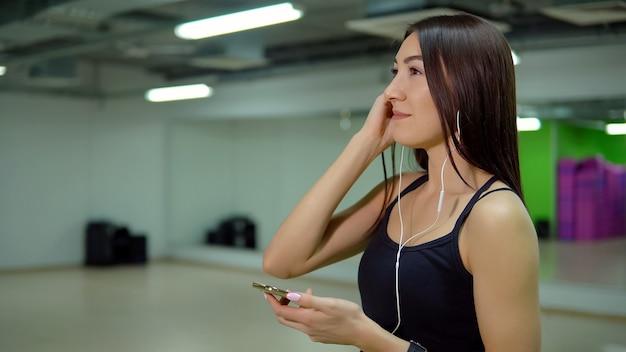 フィットネスのコンセプト。電話とジムでヘッドフォンでスポーツユニフォームを着た若い女性。