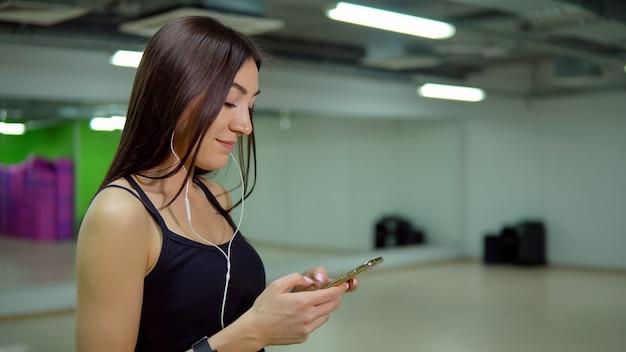 피트니스 개념입니다. 체육관에서 전화와 헤드폰을 끼고 스포츠 유니폼을 입은 젊은 여성