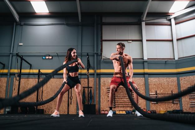 팔 밧줄 운동을 하는 30대 소년과 소녀의 피트니스 커플