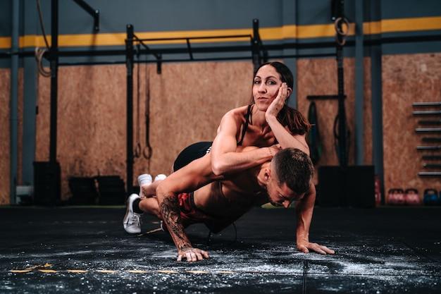 문신을 한 소년과 소녀의 피트니스 커플, 근육을 키우기 위해 체육관에서 열심히 일하는 30대