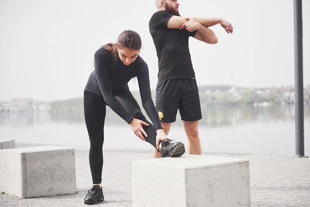 물 근처 공원에서 야외에서 스트레칭 피트 니스 커플. 젊은 수염 남자와 여자는 아침에 함께 운동