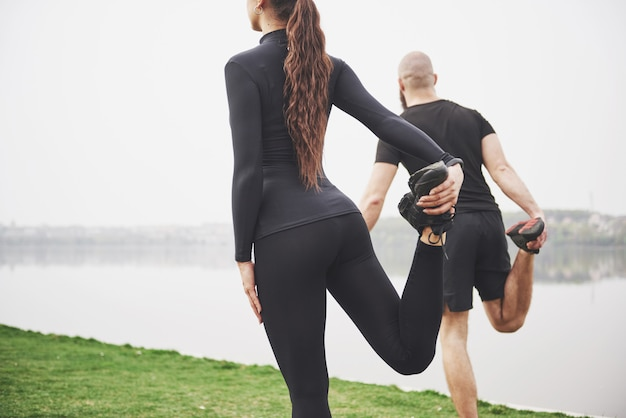 Fitness couple stretching outdoors in park near the water. young bearded man and woman exercising together in morning