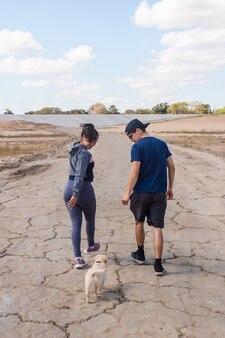 ビーチで愛らしい子犬の隣を歩いているフィットネスカップル。