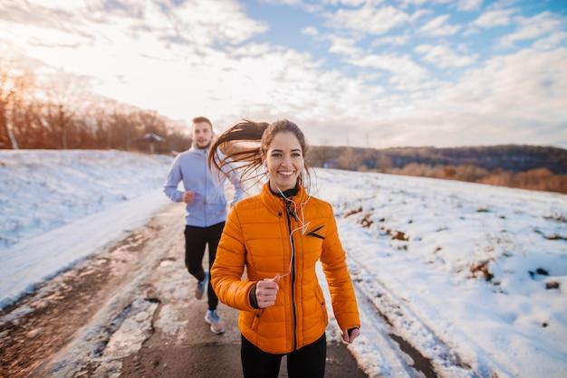 フィットネスカップル冬の朝は雪に覆われた山で運動します。
