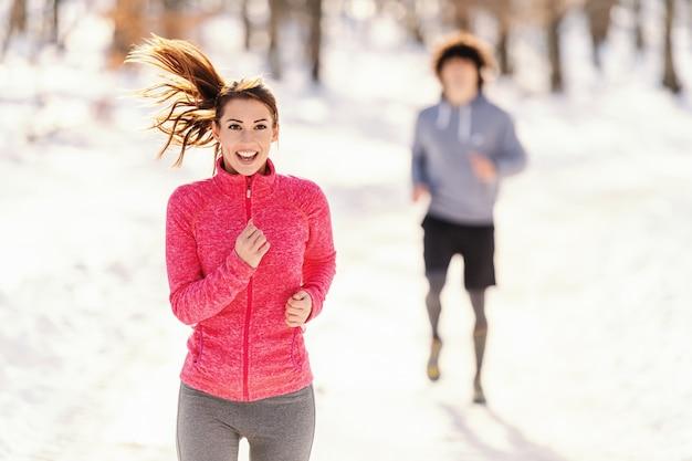 フィットネスカップル冬の朝の体操。冬のフィットネスの概念。