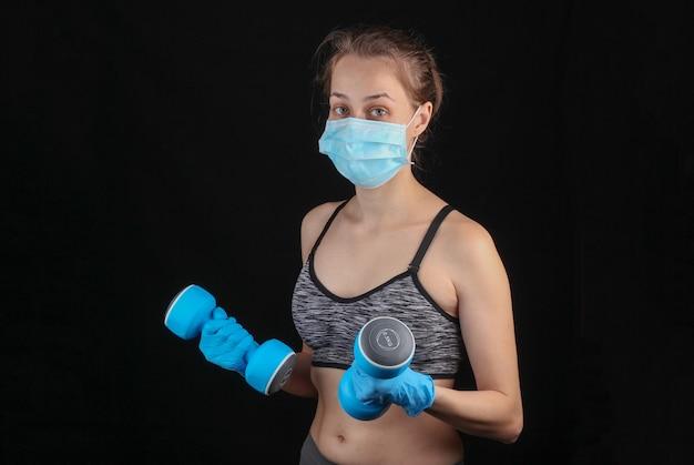Covid-19 대유행 격리 중 피트니스. 의료 마스크와 장갑에 체육 여자 검은 벽에 그녀의 손에 아령을 보유하고있다.