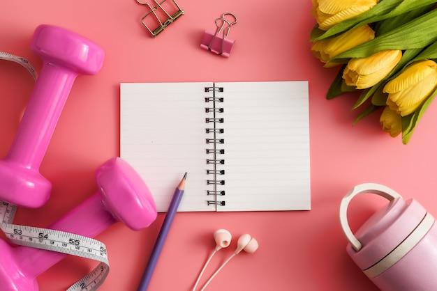 피트 니스 장비 아령 메모장 연필과 분홍색 배경에 이어폰.