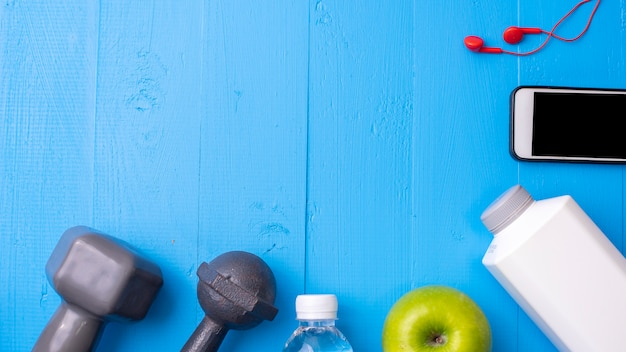 Fitness equipment and health food on blue wooden background