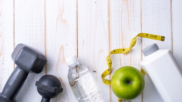 Fitness equipment and health food on white  wooden background