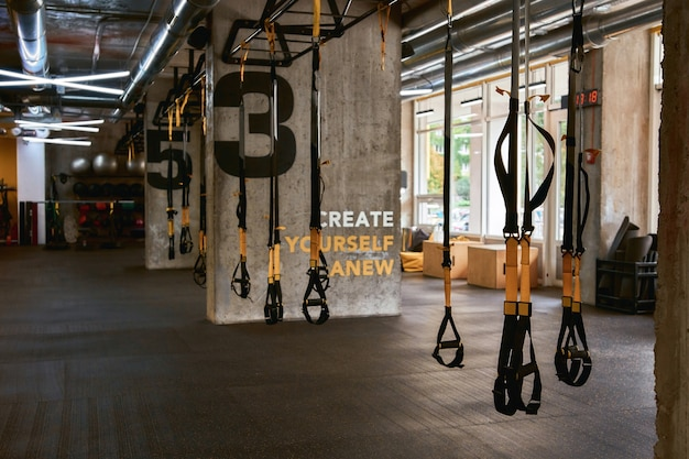 Fitness equipment. trx straps inside of a gym, functional training and sport accessories. active lifestyle, fitness and crossfit concept