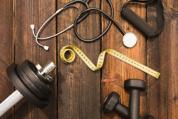 Fitness equipment with stethoscope and measuring tape on wooden surface