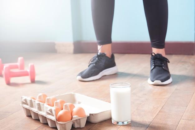 Fitness femminile in pantaloni neri in piedi sul pavimento di legno con manubri e prodotto lattiero-caseario per allenamento con copia spazio