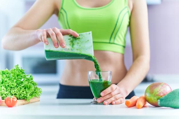 녹색 스무디를 마시는 피트 니스 여성. 건강한 식습관을위한 야채 해독 유기농 다이어트 음료