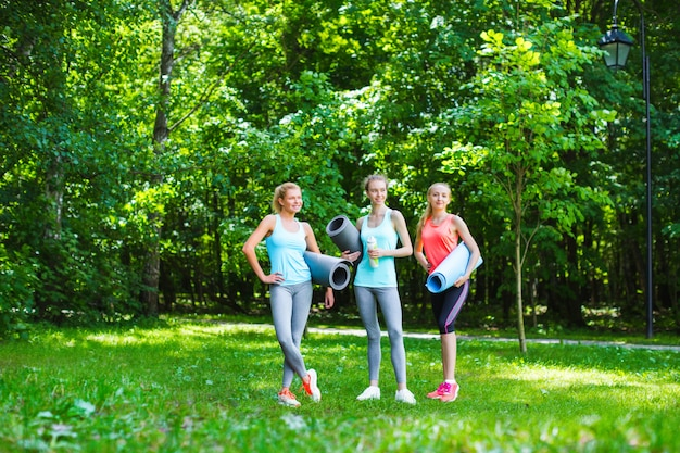 Fitness female group in park on a sunny day. workout outdoors.