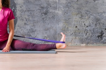 Fitness female model doing stretching workout with resistance band