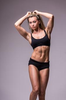 회색 배경에 스포츠웨어 피트니스 여성 모델