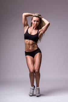 Женская модель фитнеса в спортивной одежде на сером фоне