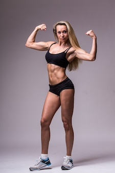 Modello femminile di fitness in abiti sportivi su sfondo grigio
