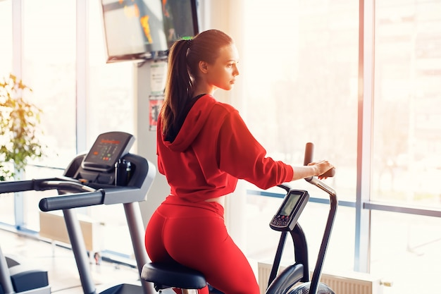 Fitness female using air bike for cardio workout at gym.