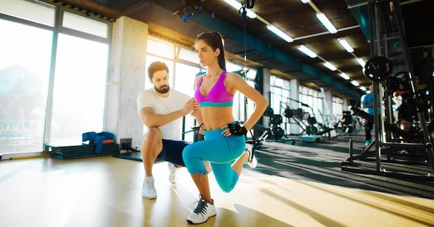Фитнес гибкая девушка делает растяжку ног с веревкой сверху и помогает личного тренера в тренажерном зале.