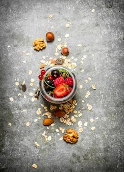 Фитнес-питание. ягоды с мюсли и орехами. на каменном столе.