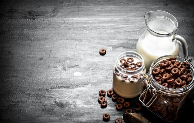 피트니스 음식. 우유와 초콜릿 조각. 검은 나무 테이블에.