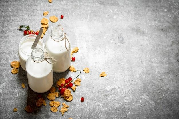 Фитнес-питание. молоко с хлопьями и ягодами. на каменном столе.
