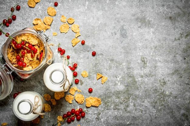 フィットネスフード。石のテーブルにベリーと牛乳とミューズリー。