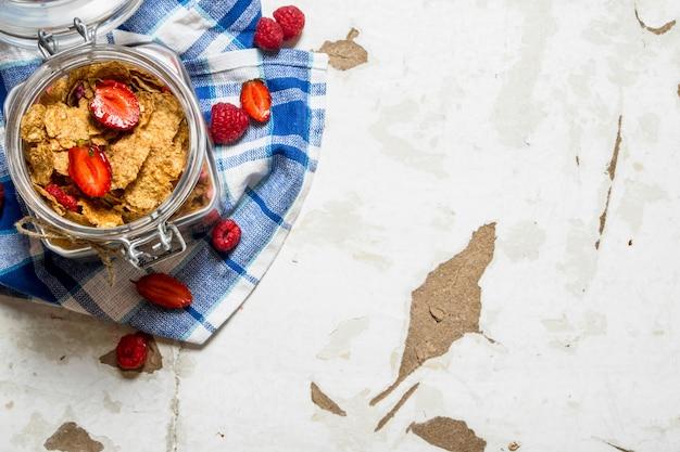 Фитнес-питание. мюсли с ягодами в банке на ткани. на деревенском фоне.