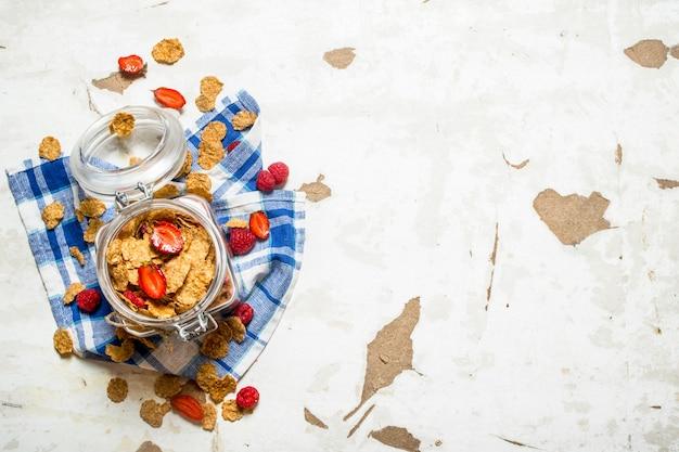 피트니스 음식. 직물에 항아리에 딸기와 뮤 즐리. 소박한 배경.