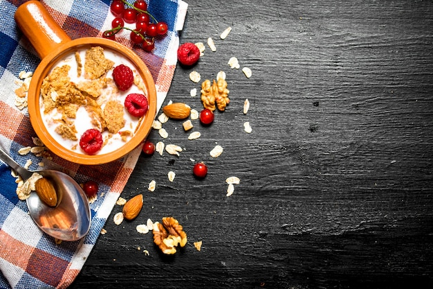 Fitness food. muesli with berries, nuts and milk in the bowl on black wooden table.