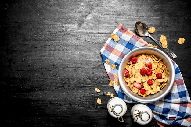 Fitness food. muesli with ripe berries and milk on black wooden table.