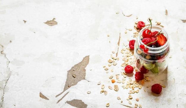 Фитнес-питание. спелые лесные ягоды с овсом. на деревенском столе.
