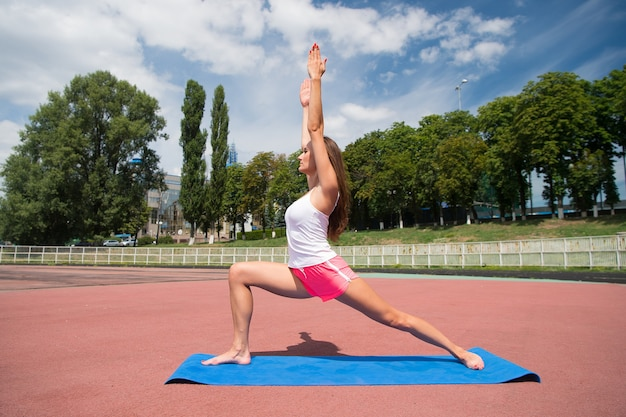 Фитнес для решения проблем здоровья. сексуальная женщина пригонки, развивающая физическую форму путем растяжения. спортивная (ый) девушка делает фитнес упражнения на стадионе. довольно спортсменка наслаждается фитнесом на открытом воздухе летом.