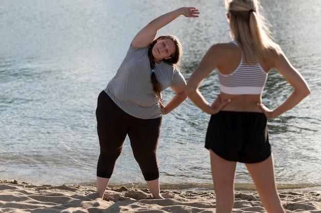 海岸でトレーニングフィットネスの友人