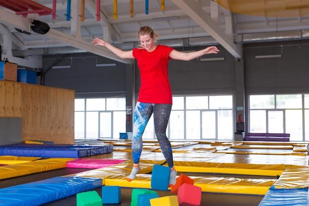 Фитнес, развлечения, досуг и концепция спортивной деятельности - молодая счастливая женщина прыгает на батуте в помещении.