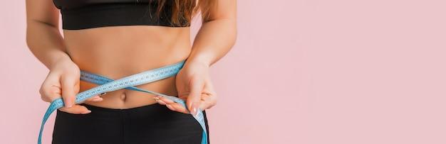 フィットネスの女の子とピンクの背景に黒のスポーツウェアでウエストを測定します。美しいアスリートボディと日焼けした肌を持つスリムな女性